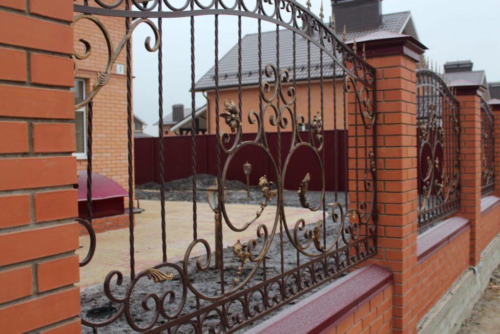 Кованый забор с кирпичными столбами